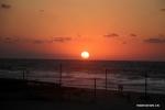 فلسطينيون يستمتعون بغروب الشمس على الشاطئ في مدينة غزة .jpg